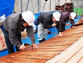 口には竹釘をくわえ、手には屋根金槌を持ち、平葺皮を用いて屋根を葺いています。